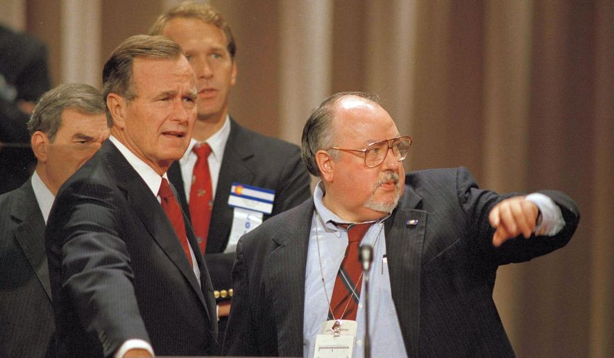 In this Aug. 17, 1988 file photo, Vice President George H.W. Bush, left, gets some advice from his media advisor, Roger Ailes, right, as they stand behind the podium at the Superdome in New Orleans, La., prior to the start