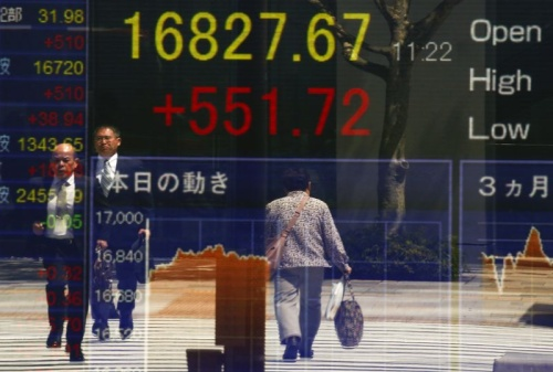 People are reflected in a screen displaying the Nikkei average outside a brokerage in Tokyo