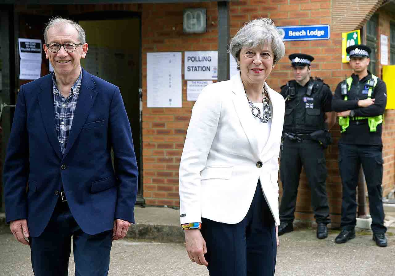 British Prime Minister Theresa May leaves with her husband, Philip, after voting in the general election at a polling station in Maidenhead, England, on Thursday.