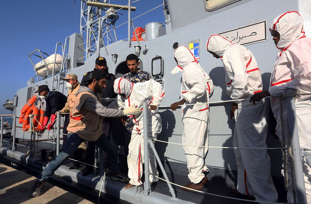 African migrants arrive at a naval base in Tripoli on Nov. 25
